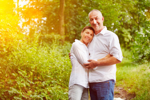 Happy smiling senior couple standing in a forest in summer