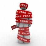 a person wrapped in red tape that says fear