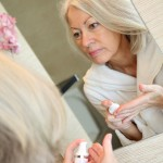 woman over 50 looking in the mirror getting ready