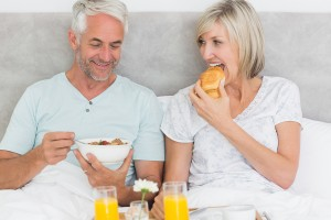 Happy mature couple having breakfast in bed at home