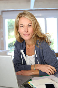 Middle aged blond woman at home with laptop