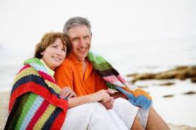couple over 50 snuggling on the beach